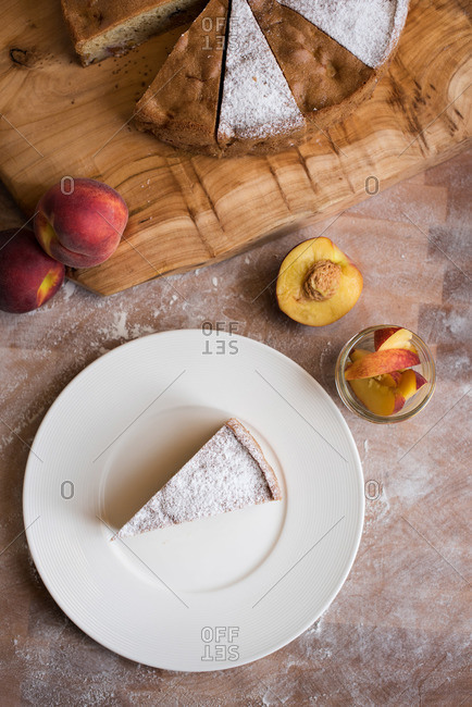 Overhead view of serving of peach cake on plate next to fresh peaches and cake on cutting board