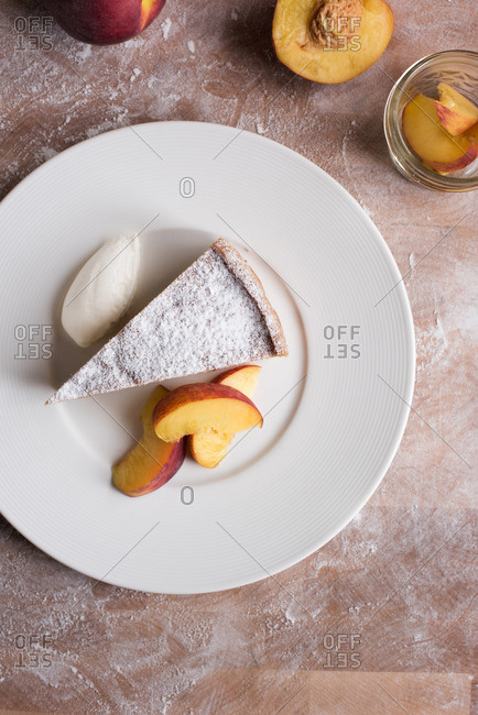 Overhead view of slice of peach cake served with cream and fresh peach slices