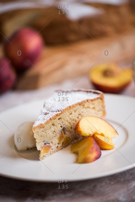 Wedge of peach cake served with cream and fresh peaches