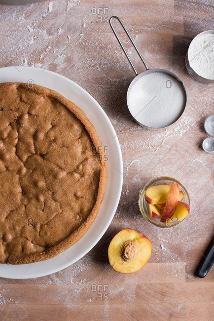 Fresh peach cake on wooden surface with measuring cups of sugar and flour and fresh peaches