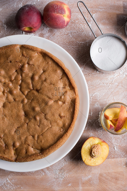 Fresh peach cake on wooden surface with measuring cup of sugar and fresh peaches