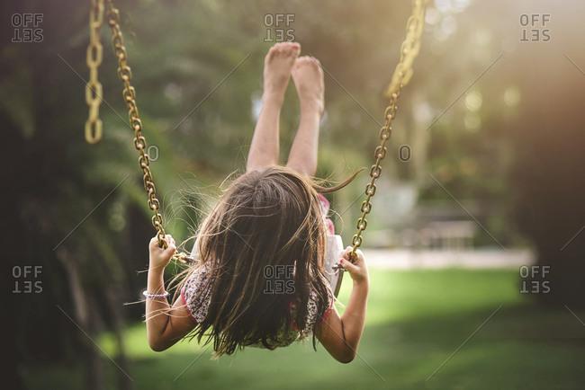 Girl in mid swing on swingset in sunlight