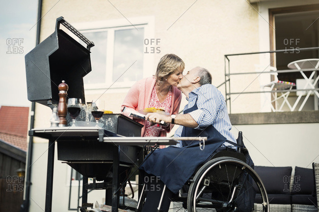 Disabled man in wheelchair kissing woman while barbecuing at yard