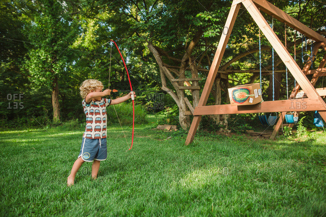 Little boy using a bow and arrow