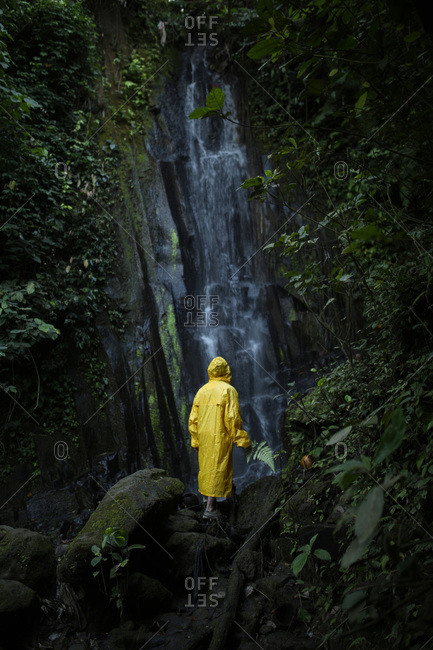 Man in a yellow raincoat hiking in a forest