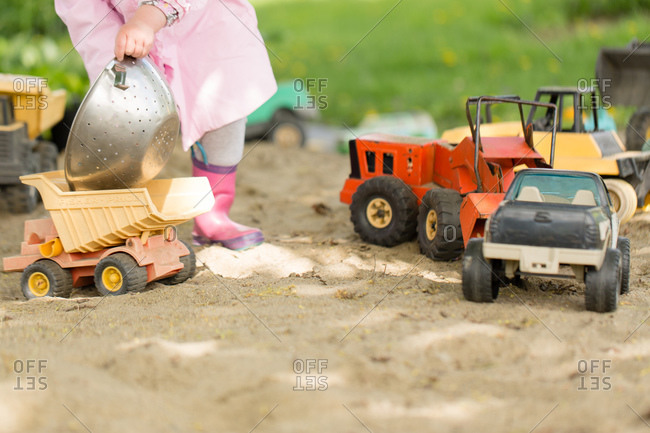 Girl playing with trucks in a sandbox