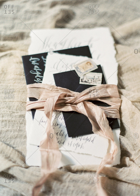 Wedding invitation and poetry with a ribbon wrapped around it