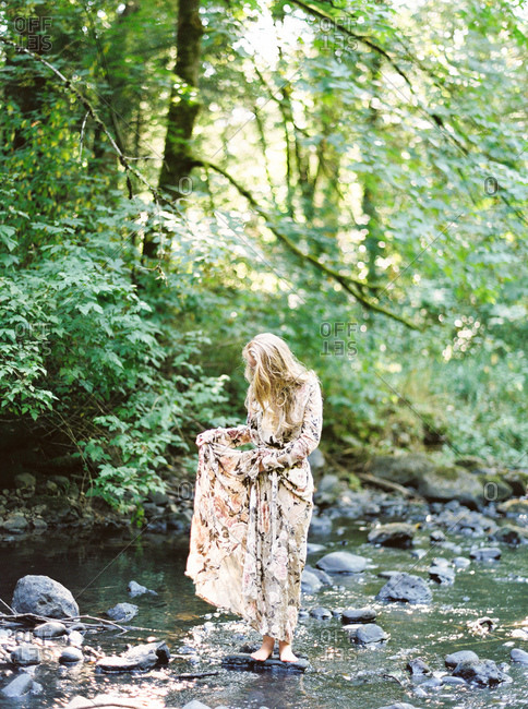 Blonde woman standing on a rock in a creek