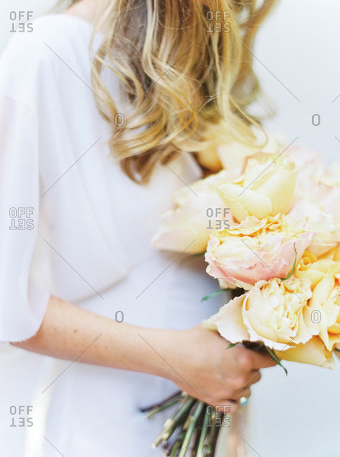 Bride holding bouquet of yellow roses