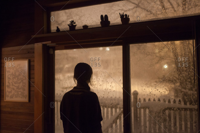Woman silhouetted in window watching snow fall