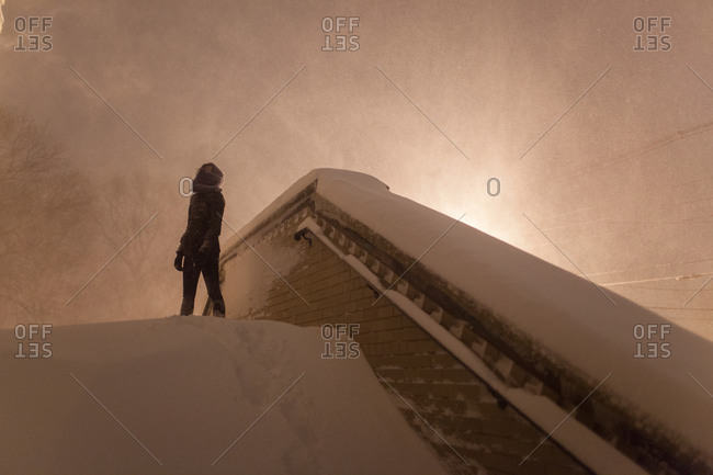 Woman at top of street stairs as snow falls