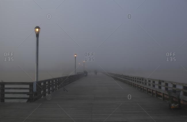 Lights illumination boardwalk on a misty beach