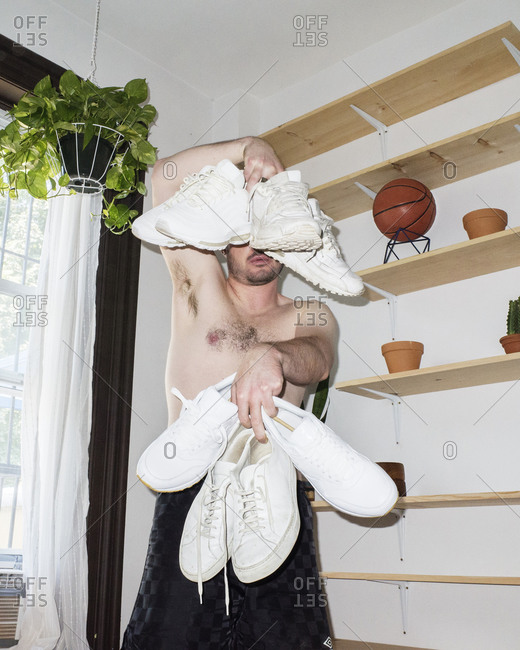 Man holding several pairs of white shoes