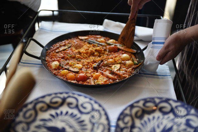 Person scooping serving of paella