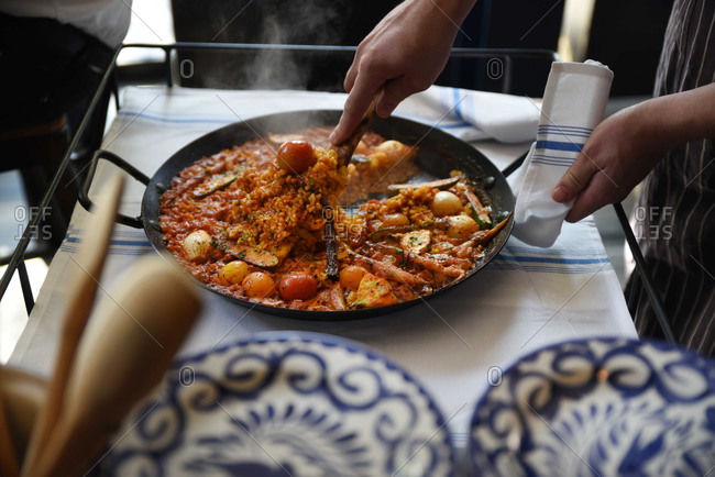 Person serving up paella