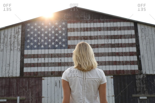 Woman looking at American flag painted on barn