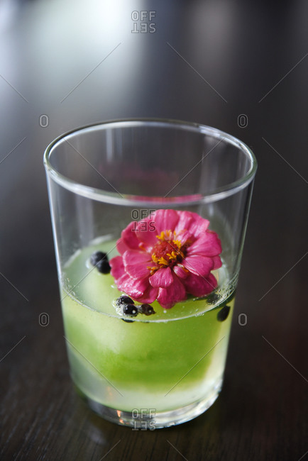 A half-full cocktail with zinnia flower