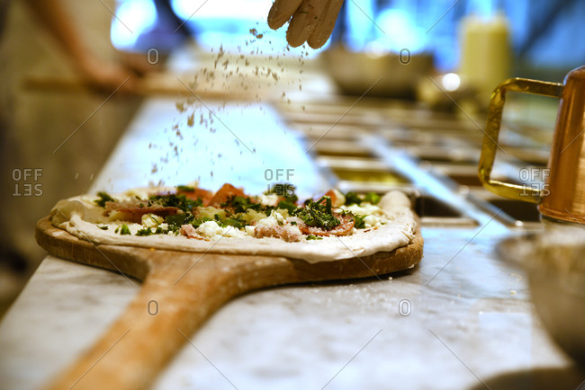 A chef sprinkling toppings on raw pizza