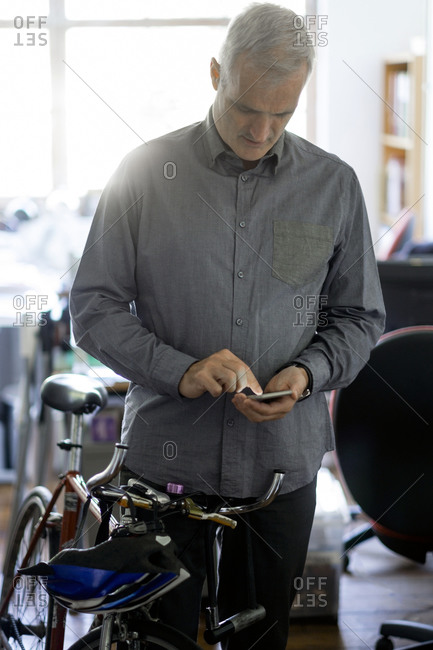 Office worker with his bike and smartphone