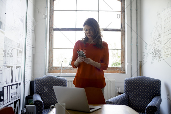 Businesswoman with a smartphone and laptop