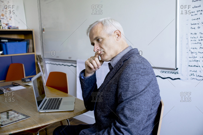 Businessman with laptop deep in thought