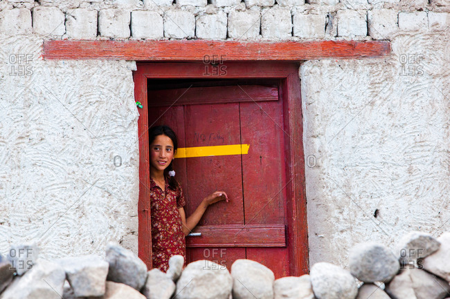 Thiksey, Ladakh, India - August 26, 2010: Young girl looking out from a door of a house in Thiksey, Ladakh