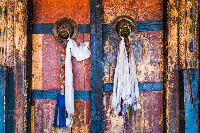 Cloths tied to colorfully painted door handles