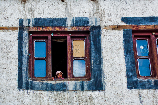 Thiksey, Ladakh, India - August 29, 2010: Young child looking out window of house in Thiksey, Ladakh, India