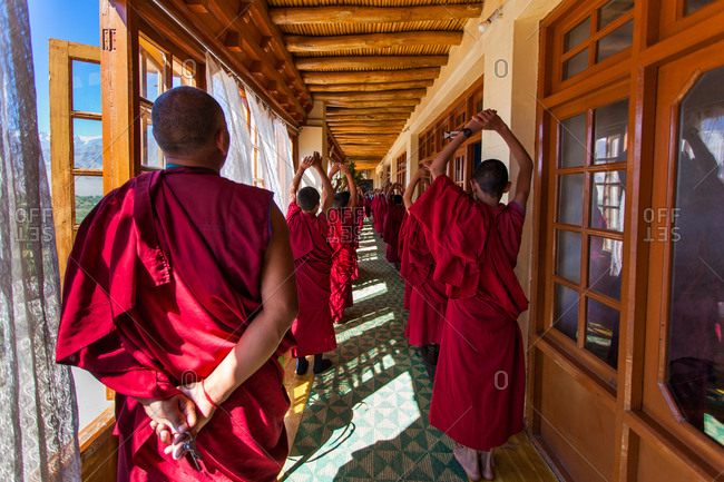 Thiksey, Ladakh, India - August 30, 2010: Group of Buddhist monks exercising in hallway of Thiksey Gompa in Ladakh, India