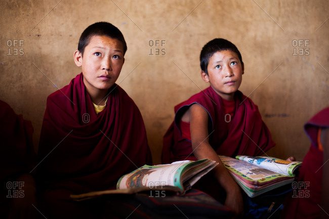 Thiksey, Ladakh, India - August 30, 2010: Two young Buddhist monks with school books listen to lesson in their classroom