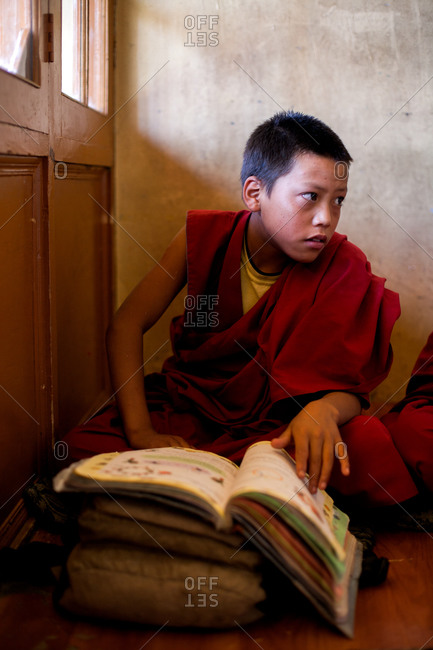 Thiksey, Ladakh, India - August 30, 2010: Young boy in Buddhist monk robes sits with a school book in monastery classroom