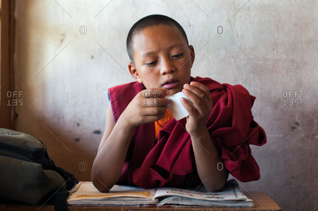 Thiksey, Ladakh, India - August 30, 2010: Young monk sits at a desk in classroom at Thiksey Gompa in Ladakh, India