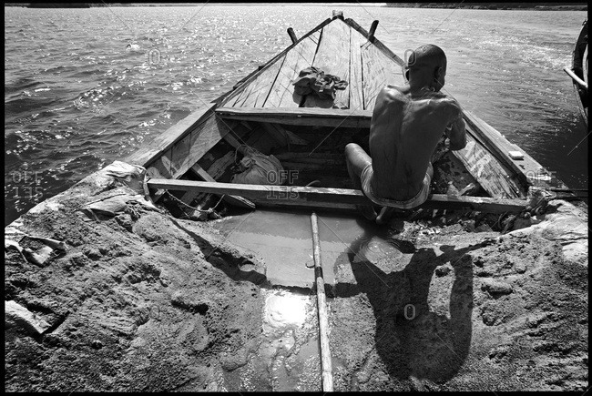 Man with sand cargo riding boat in Mali