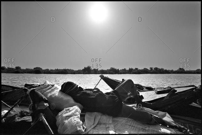 Man with sand cargo sleeping on boat, Mali