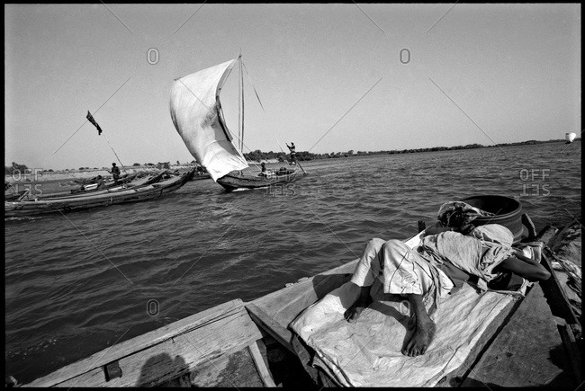 Man with sand cargo sleeping on boat in Mali