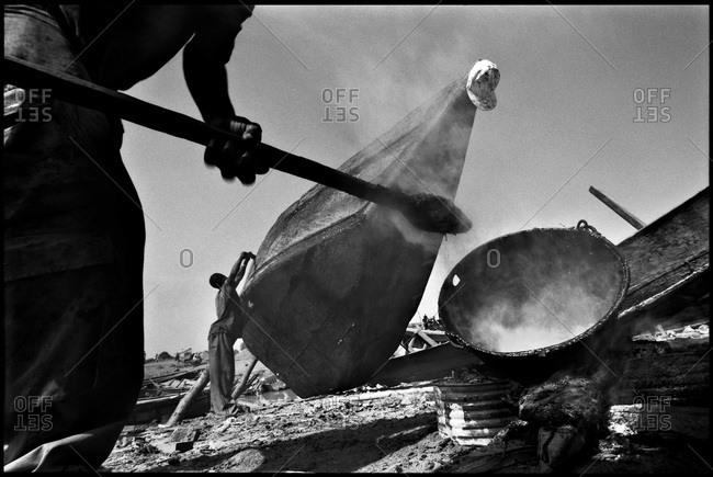 Man heating tar for boat repair, Mali