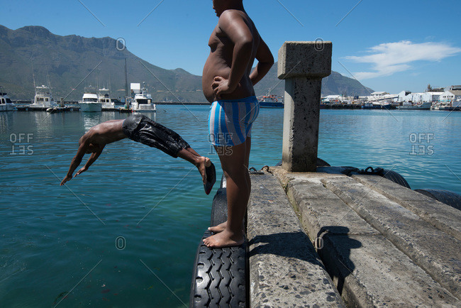 Man and a boy diving off pier on African coast