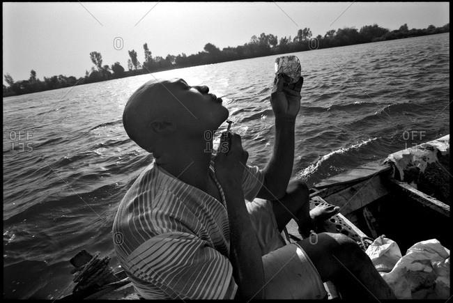 Bamako, Mali - June 8, 2011: Sand fisherman shaving while on boat, Mali