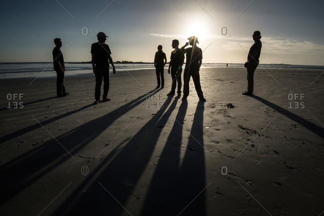 Cape Town, South Africa - February 18, 2015: Six men and their shadows on South African beach