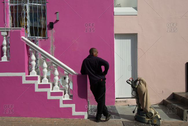 Cape Town, South Africa - February 19, 2015: Man waiting outside building in Cape Town, South African neighborhood