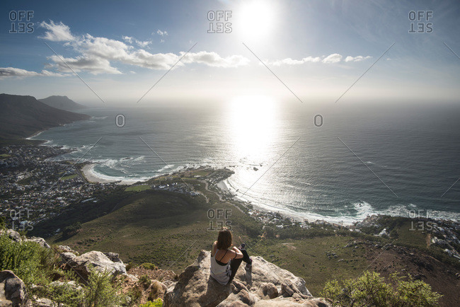 Woman looking over rugged South African coast
