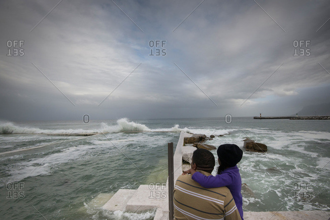 Two people looking out to ocean waves in Muizenberg, South Africa