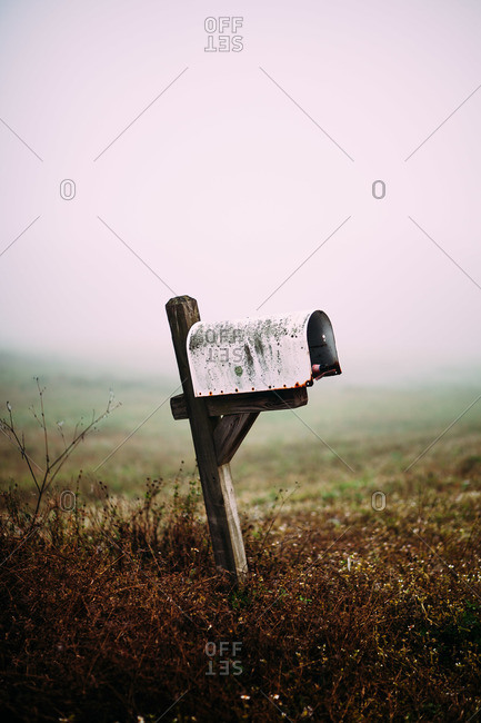 Weathered mailbox on post containing a beer bottle