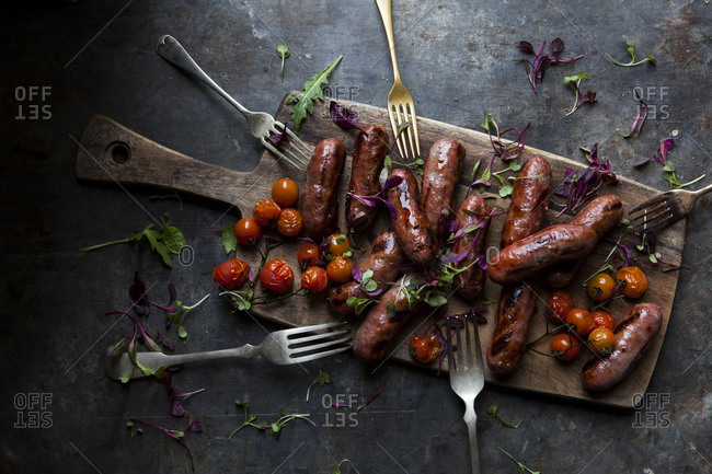 Sausages and grilled tomatoes garnished with microgreens