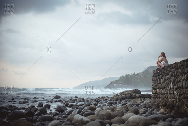 Woman sitting on rock wall and gazing at ocean