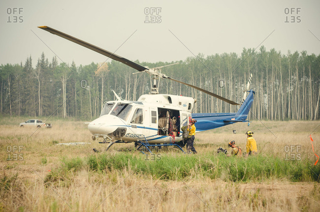 Alberta, British Colombia, Canada - July 12, 2015: Helicopter being loaded by Panorama Crew Services members, Alberta, British Colombia, Canada