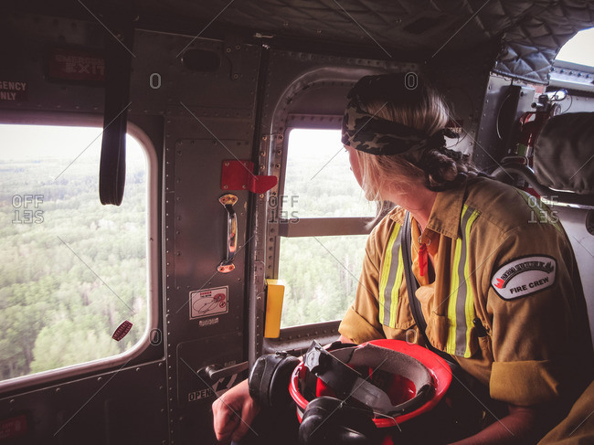 Alberta, British Colombia, Canada - July 13, 2015: Female Panorama Crew Services member looking out the window of helicopter, Alberta, British Colombia, Canada