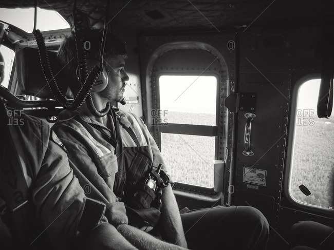 Alberta, British Colombia, Canada - July 13, 2015: Black and white male Panorama Crew Services member looking out the window of helicopter, Alberta, British Colombia, Canada