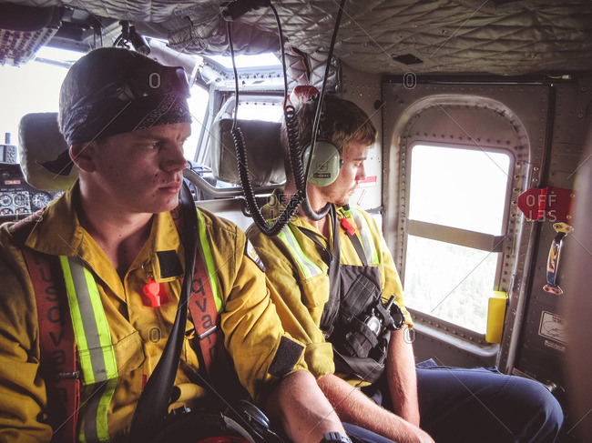 Alberta, British Colombia, Canada - July 13, 2015: Two male Panorama Crew Services members looking out the window of helicopter, Alberta, British Colombia, Canada