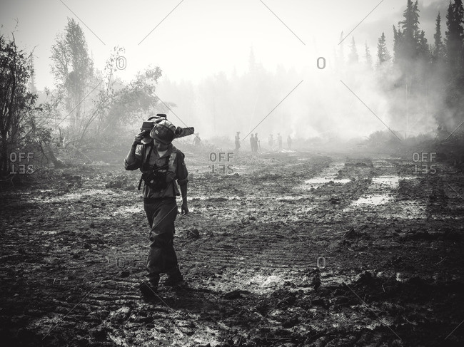 Alberta, British Colombia, Canada - July 13, 2015: Panorama Crew Services member carrying chainsaw on his shoulder, Alberta, British Colombia, Canada